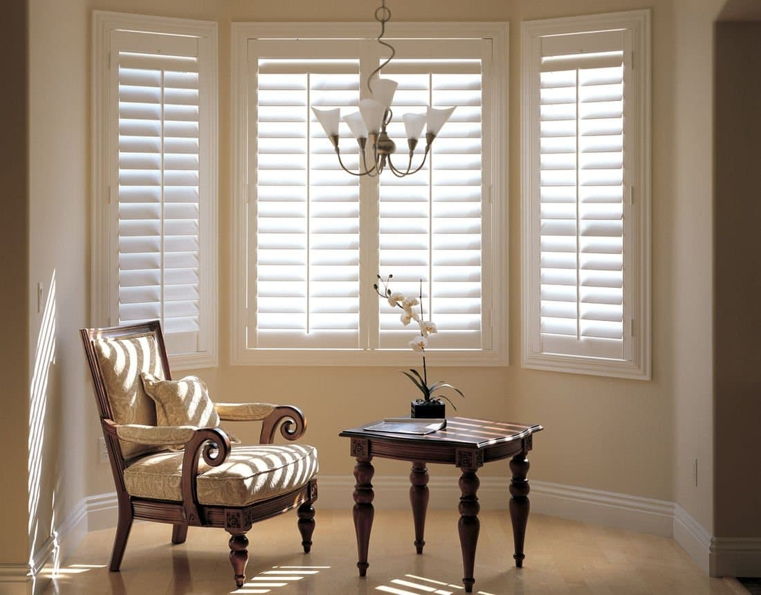 A chair and a small table in front of plantation shutters.